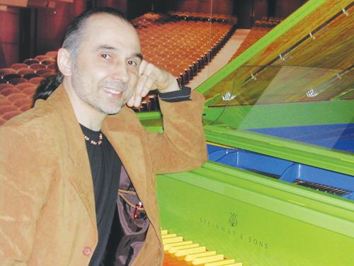Piano tuner Yuri Melekh sits in front of a green Steinway & Sons piano.