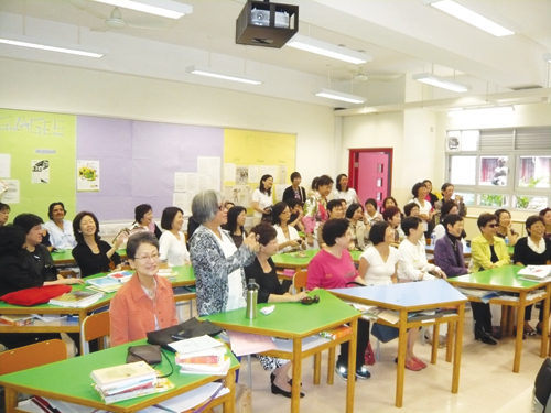 Assunta Ng (foreground, peach jacket) sits among her former Sacred Heart Canossian College classmates in a classroom during their 40-year reunion in Hong Kong. (Photo by John Chan)
