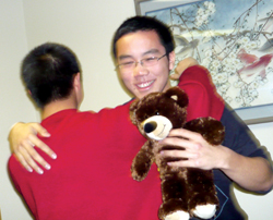 Brandon Lee (left) gives Alan Leung a stuffed bear for Christmas. Lee gets a hug from Leung in return (Photo by Assunta Ng/NWAW)