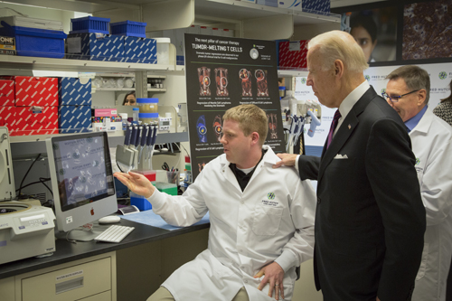 Vice President Joe Biden chats with Joshua Veatch while visiting Dr Stan Riddell's lab during a tour at the Fred Hutchinson Cancer Research Center in Seattle, Washington on March 21, 2016. Biden is on the Cancer Moonshot listening tour in which he is visiting cancer research centers and speaking with leaders in research and care in order to focus the nation's attention and speed up cancer cancer cures.