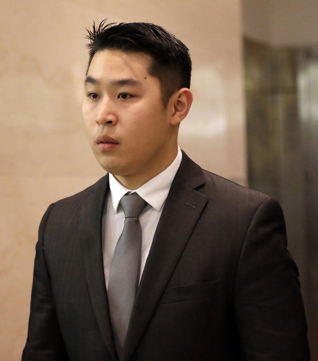 New York City rookie police officer Peter Liang, center, leaves the courtroom after he pleaded not guilty at his arraignment at Brooklyn Superior court, Wednesday, Feb. 11, 2015, in New York. Liang, who fired into a darkened stairwell last November at a Brooklyn public housing complex, accidentally killing 28-year-old Akai Gurley, has been charged with manslaughter, official misconduct and other charges. He was released without bail. (AP Photo/Mary Altaffer)