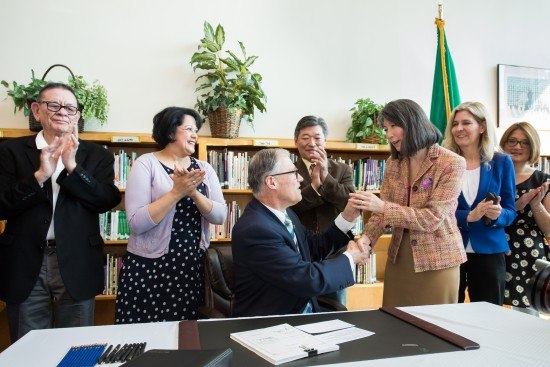 Gov. Jay Inslee signs House Bill 1541 on March 30. Bill sponsor Rep. Sharon Tomiko Santos receives the pen used to sign the measure into law.