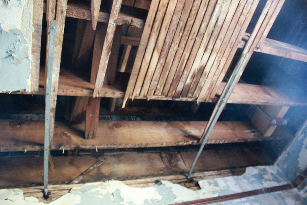 Former retrofitting attempt from 1960, using weaker, thinner ties to secure walls to floors. They weren't fastened to joists, just floorboards. (Photo by Stacy Nguyen/NWAW)