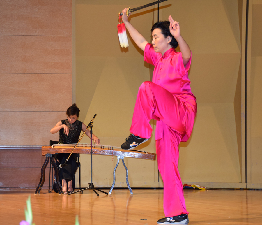 Buyun Chang playing the guzheng for Master Hong's performance. Master YiJiao Hong performing Chen Taichi Sword.