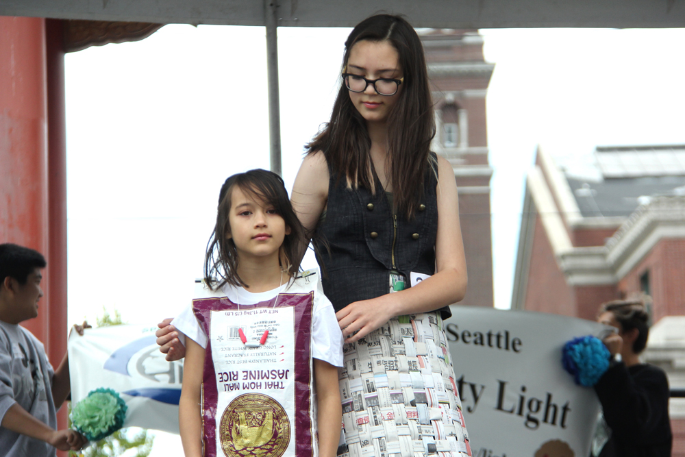 3rd place winner India Unwin (right) with sister, Hero. India's garment is a skirt woven out of recycled newspaper with a crumpled paper bustle in the back and repurposed 4th of July confetti poppers. (Photo by Eugene Tagawa)