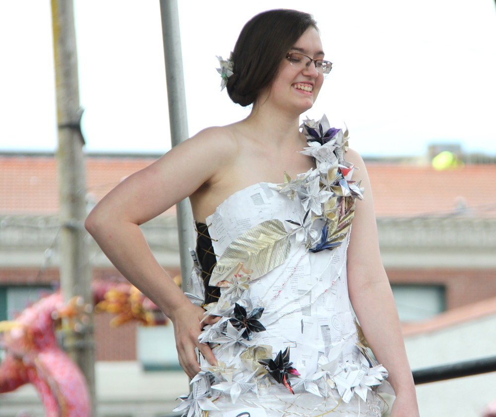 Designed by Sarenia Fought. This dress is made of white plastic bags with flowers on the paper mache bodice.
