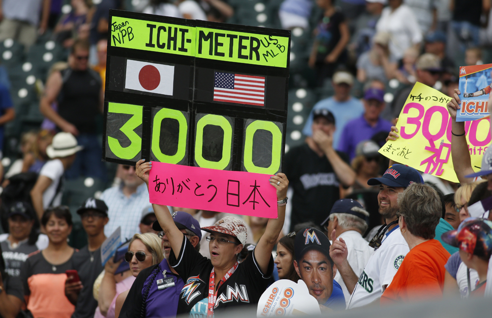 Fans hold up a sign to mark the milestone career hit. (AP Photo/David Zalubowski)