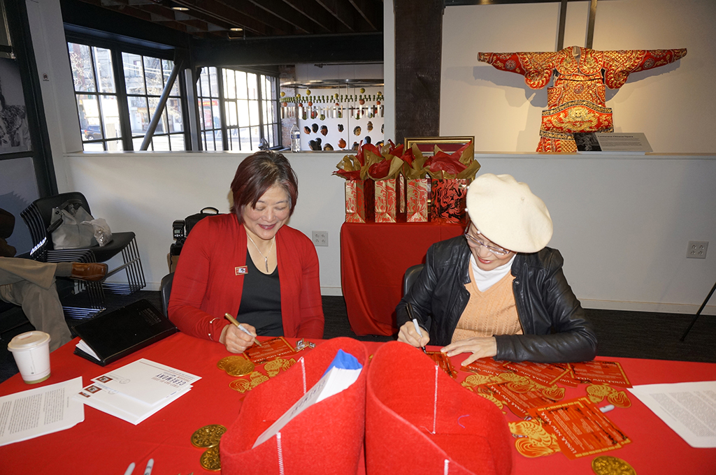 Wing Luke Museum Executive Director Beth Takekawa (left) and Publisher Assunta Ng sign souvenir sheets.