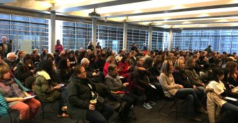 """Crowd listens intently at """"welcoming city"""" meeting"""