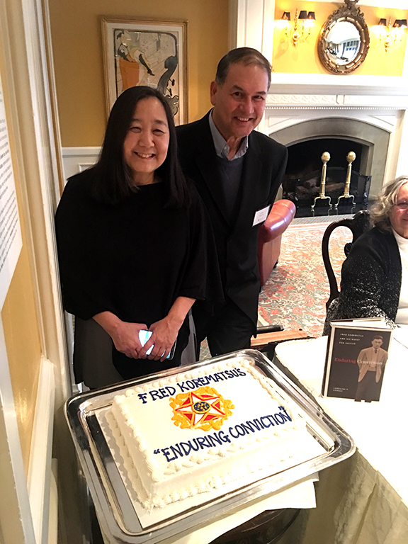 "Seattle University Law Professor Lorraine Bannai (left) and James Doane at The Rainier Club's Feb. 3 Northwest Author's Showcase luncheon for ""Enduring Conviction: Fred Korematsu's Quest for Justice."" Prof. Banai's book is placed next to the cake. (Photo by Jenn Doane)"